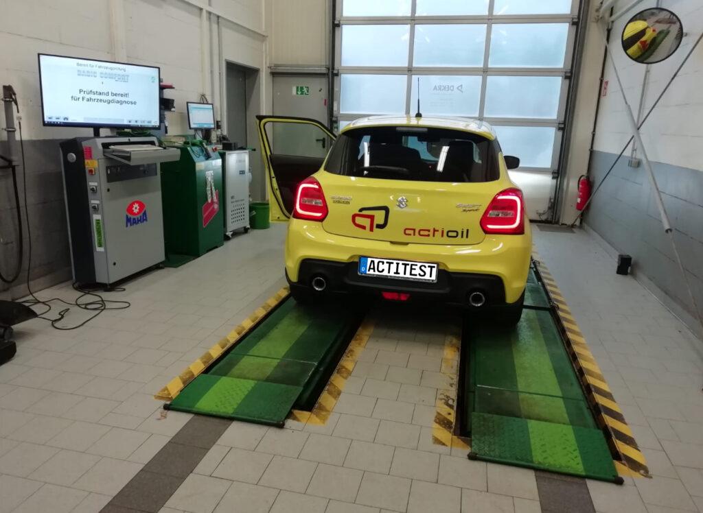 Voiture Suzuki jaune dans une zone d'essai de DEKRA. Mesure de l'efficacité du carburant et de l'environnement