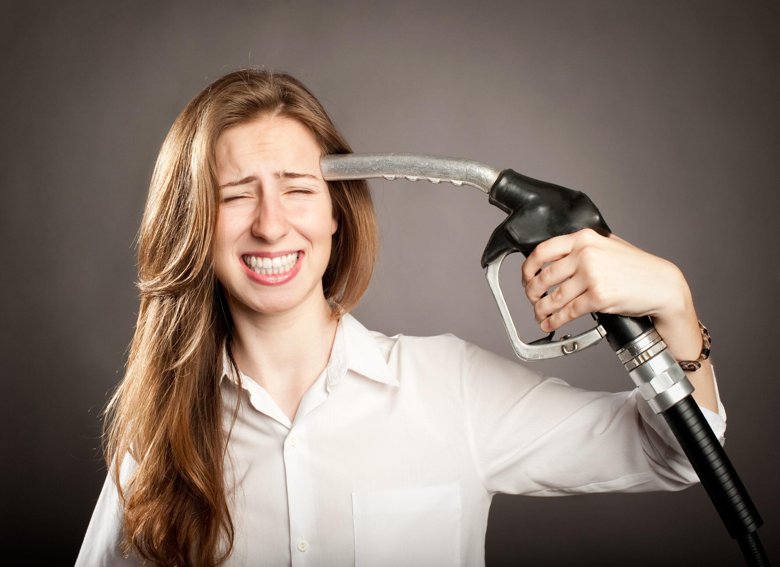 Junge Frau, die eine Tankstellenpumpe der Tankstelle auf ihren Kopf zeigt
