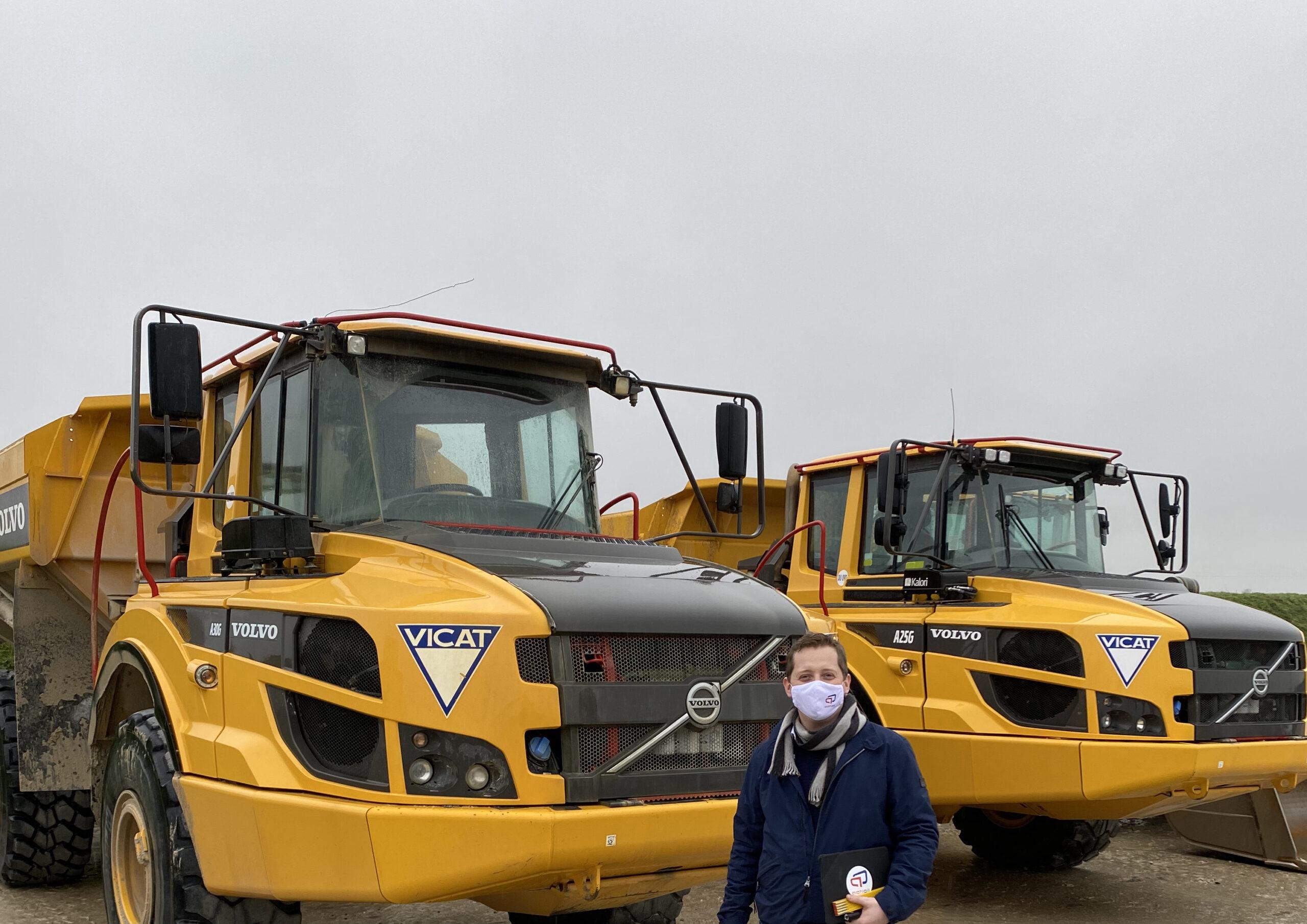 Technicien Actioil. Personne debout en face de deux camions Volvo jaune de VICAT Cement