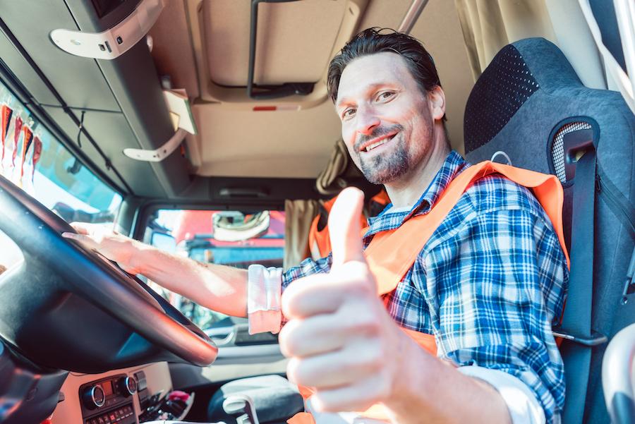 Chauffeur de camion dans son cockpit, montrant un pouce vers le haut pour Actioil